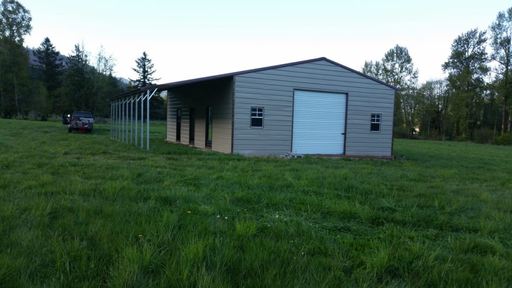 A steel building surrounded by green grass and trees, showing steel's strength in a pole barn vs. steel building comparison.