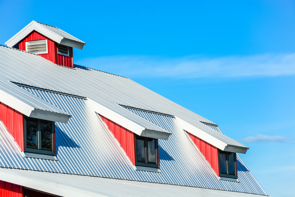 Top of a new red metal horse barn with a custom roof style