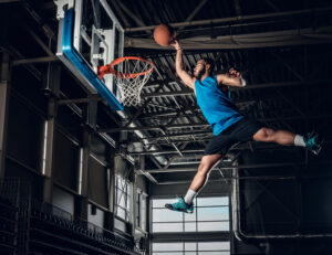 Black professional Black basketball player in action in a metal building, basketball gym.