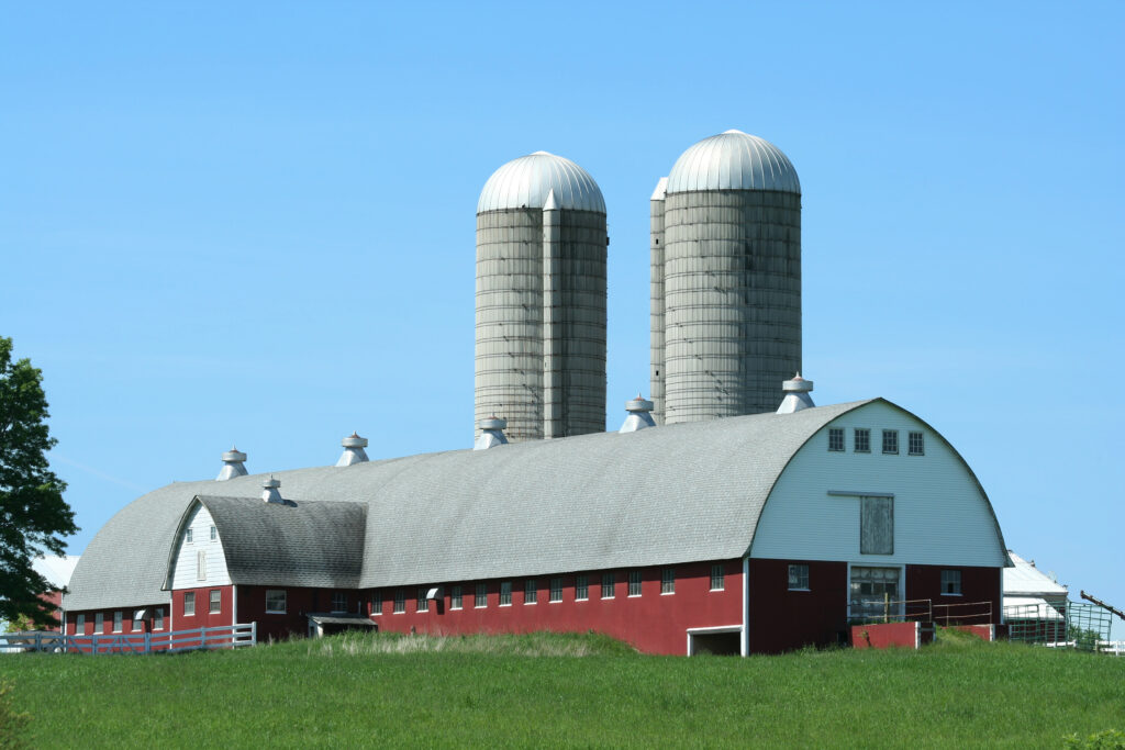 Large metal red barn with big silos