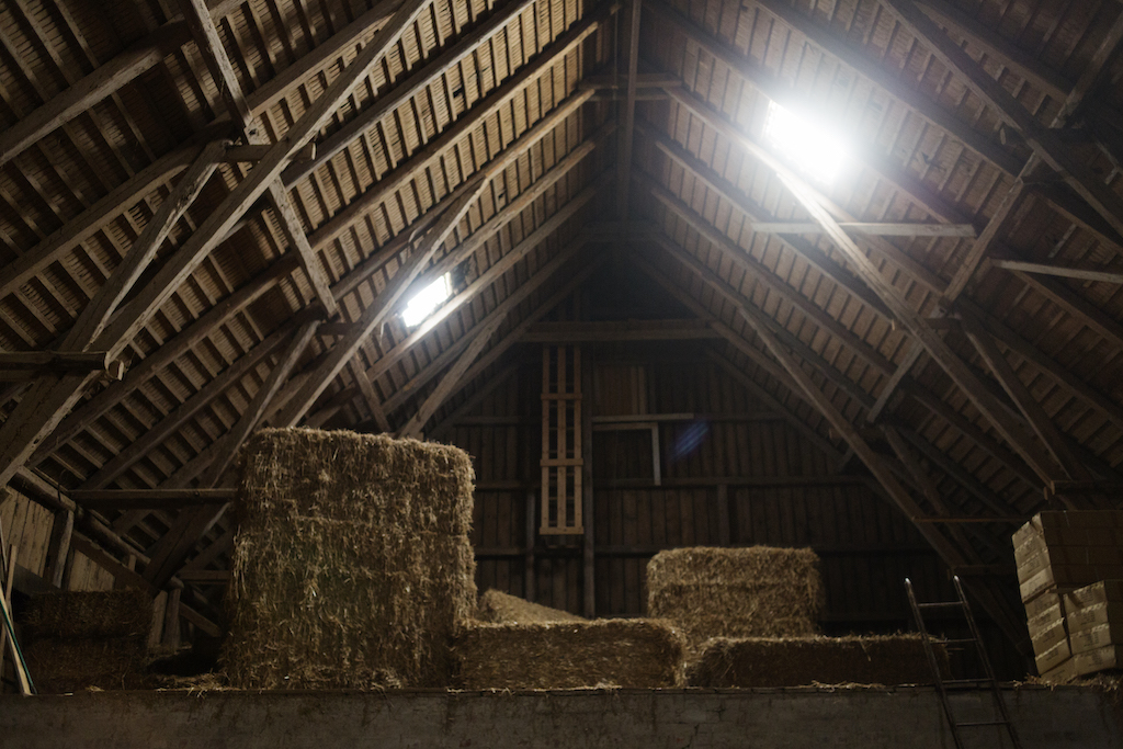 A dimly lit barn interior with a haystack, showing how metal barns can be used as hay storage buildings.