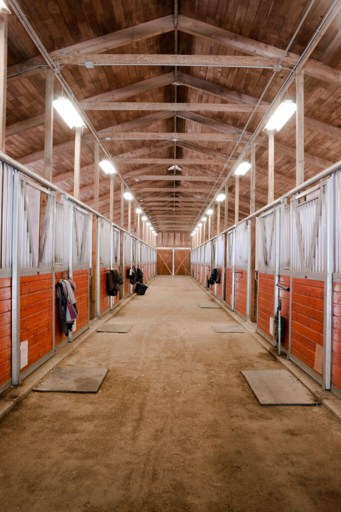 A aisle in a metal horse barn that's brightly lit